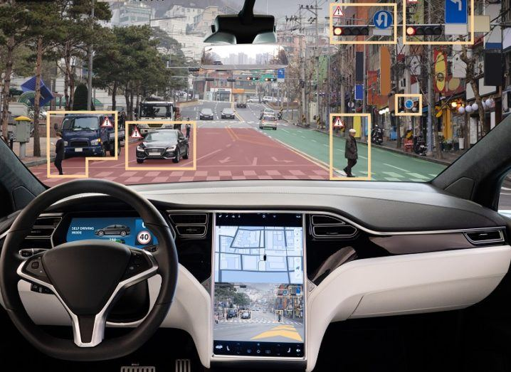 The interior of an autonomous car. Through the windscreen, we can see features on the road that have been highlighted by the car's AI system, including road signs and other vehicles.