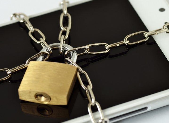 Close-up of smartphone locked with chain and padlock.