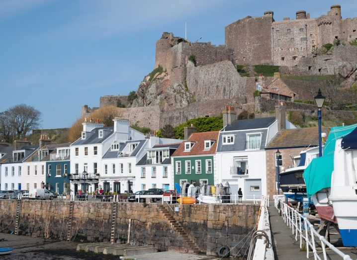 Harbour image of Gorey with a large castle above a number of homes.