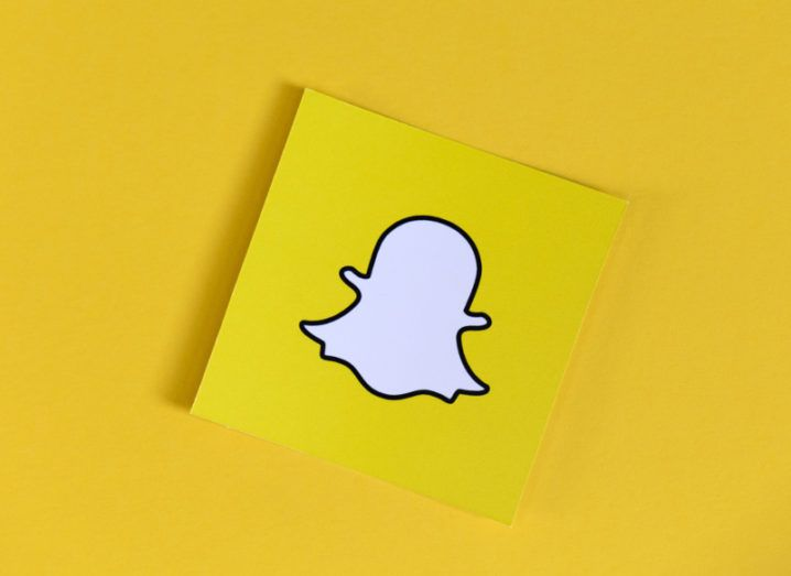 Snapchat logo on a yellow post-it note against a yellow background.