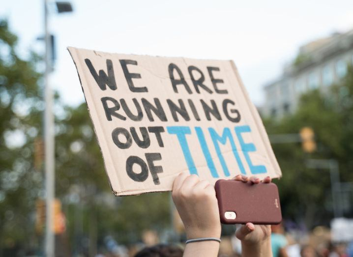A hand holds up a piece of cardboard declaring 'We are running out of time'. In the background, a crowd of people can be seen.