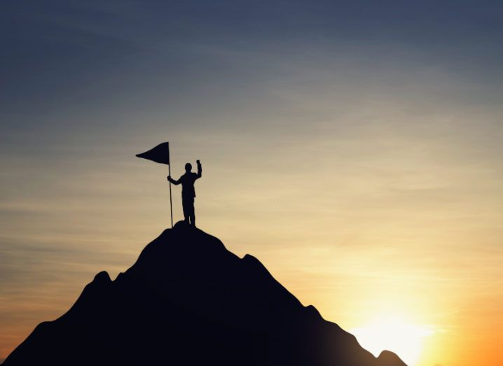 A business person standing on top of a mountain at sunset, planting a flag into the peak.