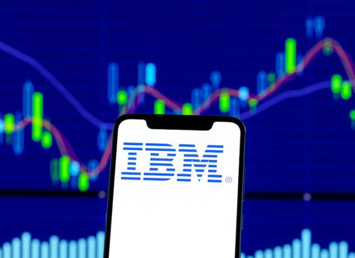 A smartphone displaying the IBM logo held up in front of a stock market chart.