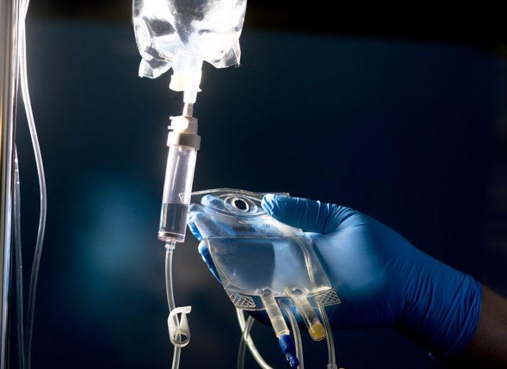 Nurse wearing a blue surgical glove holding an IV bag against a dark background.