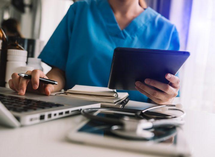 Healthcare staff in blue scrubs looking at a laptop and tablet.