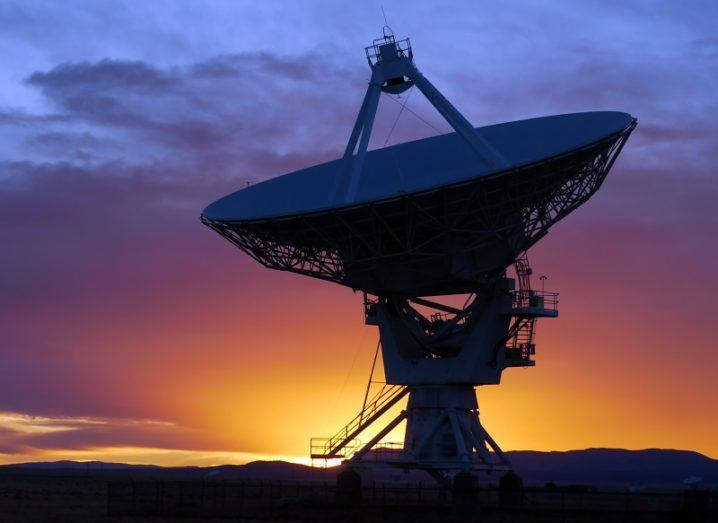 Large radio telescope against a dusk background.