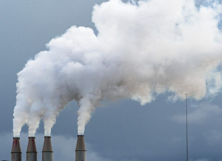 Smoke rising from four chimneys against a dark, cloudy sky.
