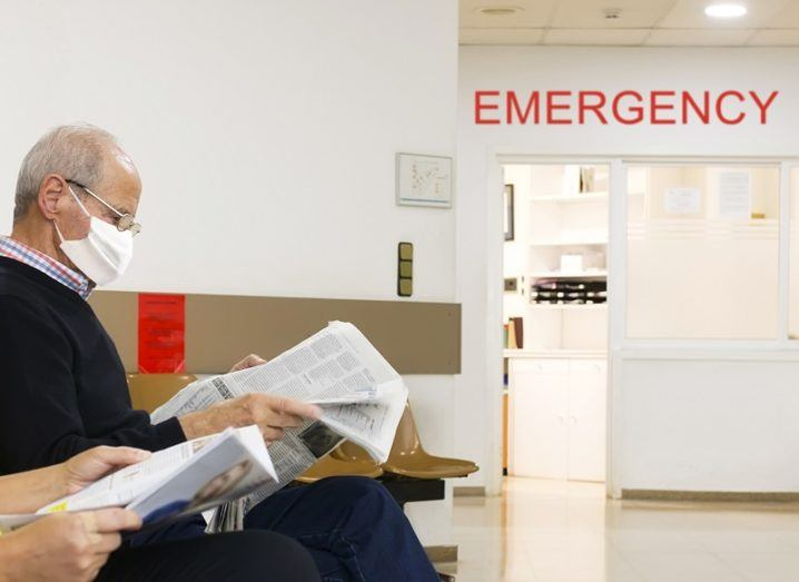 Man sitting and reading a newspaper and wearing a mask in a hospital waiting room.