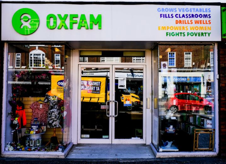 Oxfam shopfront on a UK high street with window displays of donated clothes, homewares and other bric-a-brac.