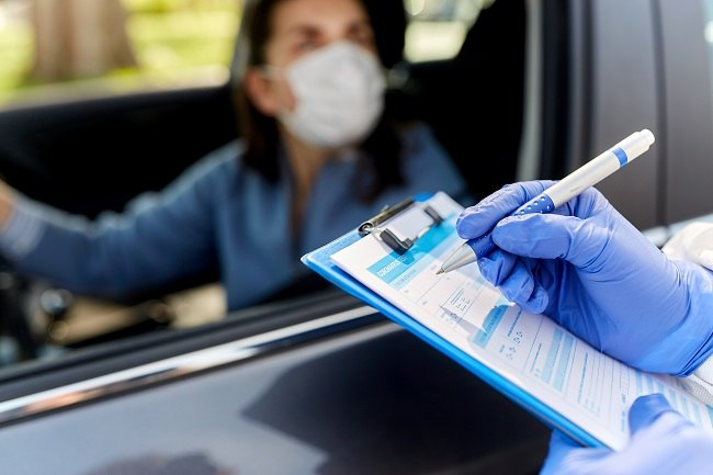 Woman wearing a face mask in a car with a person in PPE writing on a clipboard.