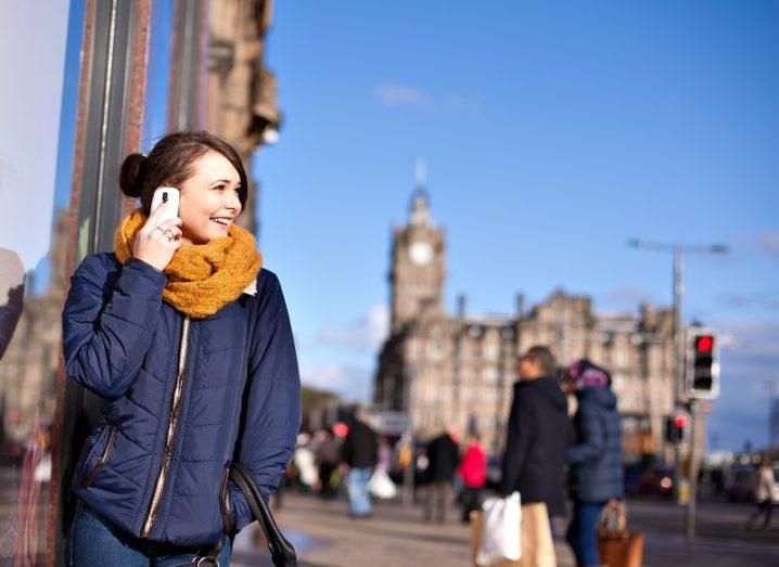 Woman smiling on the phone on an Edinburgh street.