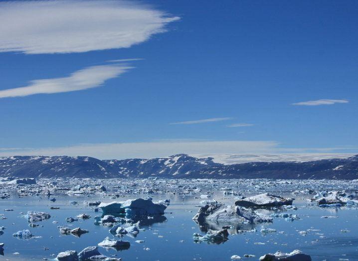 Icebergs in Greenland below a bright blue sky.