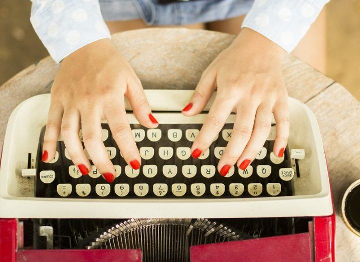 Hands striking the keys at a red and white typewriter.