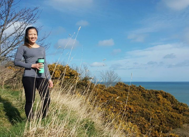 Charmaine Cruz smiling in a grey top holding a green cup overlooking coastal shrubbery and a blue sea.