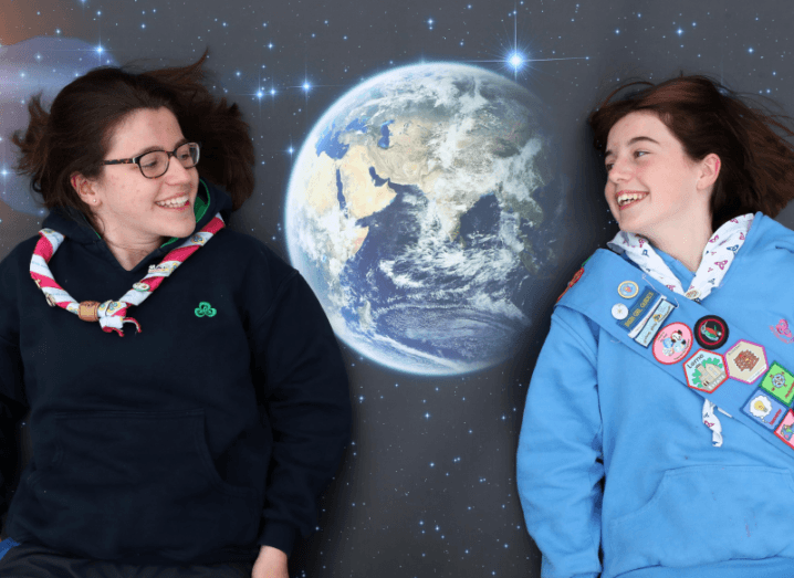 Two girls lying on top of a poster of earth. They are wearing Irish Girl Guides uniforms.