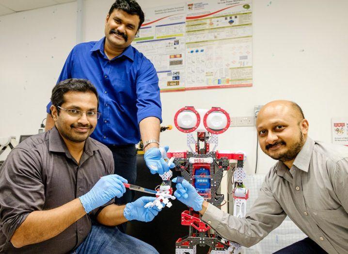 Prof Nripan Mathews, Rohit Abraham John and Arindam Basu holding a knife to the robot's AI-powered sensors.