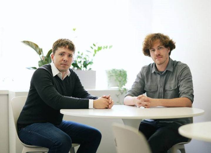 Two men in smart casual wear sit at a white table next to a window with leafy green plants on the ledge.