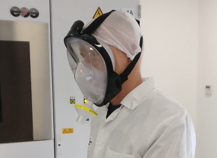 IMR researcher in full, white PPE and wearing a PMask.