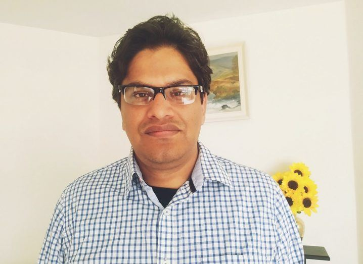 Rejwanul Haque wearing glasses and a blue and white checkered shirt against a white wall background and yellow flowers.