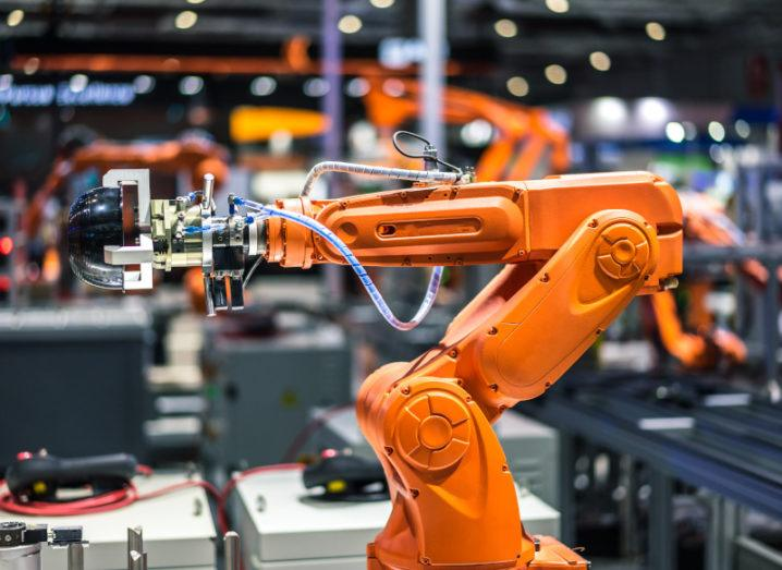 An orange robot arm in a large industrial factory.
