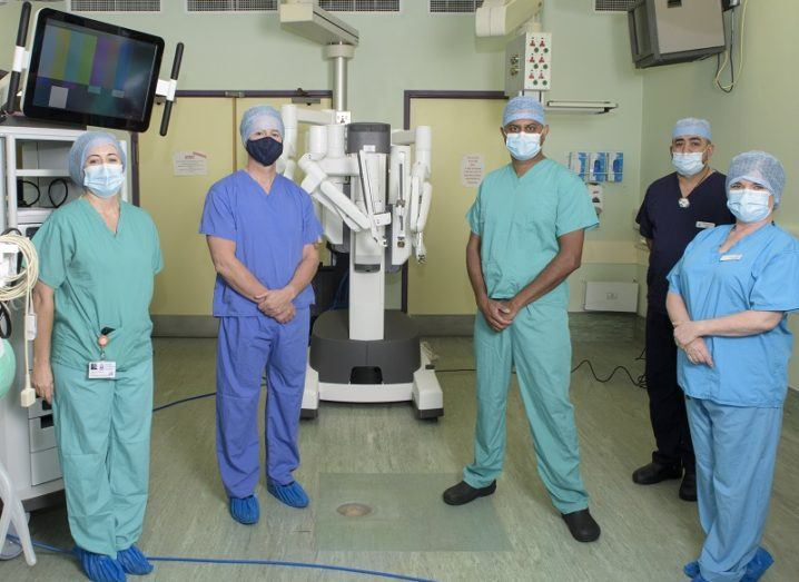Five Tallaght University Hospital staff in green and blue hospital scrubs and masks standing beside the new robot surgeon, Leona.