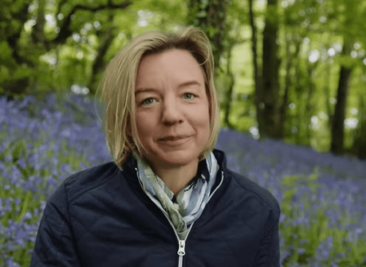 Dr Tara Shine sitting in a forest surrounded by purple flowers.