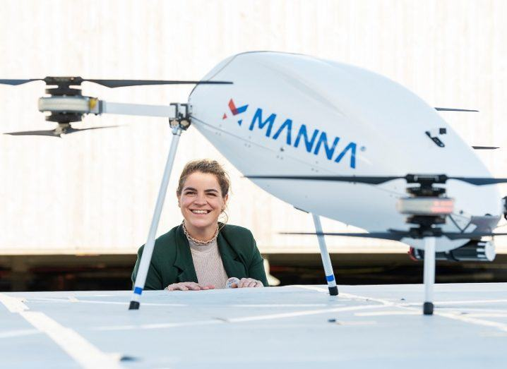 Catherine Swift smiling beside a Manna delivery drone.