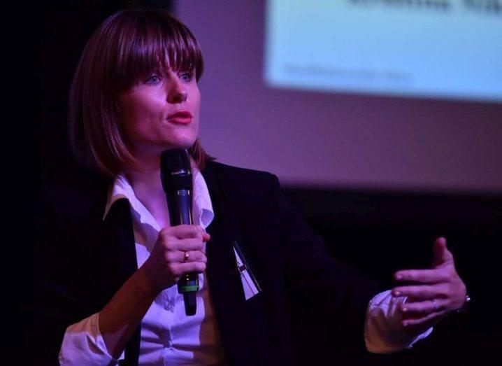 Tijana Milosevic giving a presentation on a dimly-lit stage coloured purple.