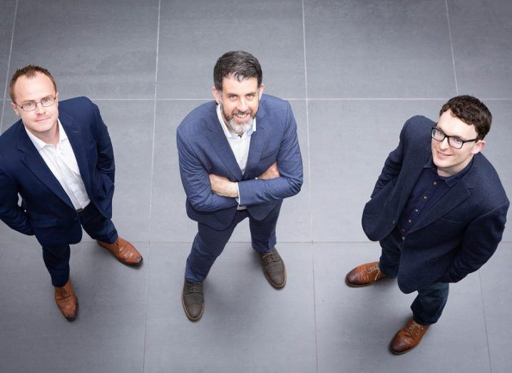 Sean Cummins, Stephen Cox and Nigel Phelan wearing suits and crossing their arms while looking up at the camera.