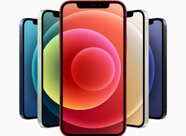Five iPhone 12 devices in a row with different colours on their screens.