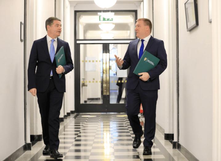 Two men walking down a corridor holding green books.