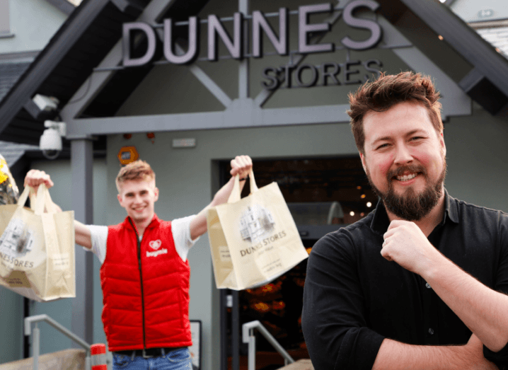 A man in a red gilet holding two shopping bags beside a man in a black shirt. Both are standing outside of a Dunnes Stores branch.