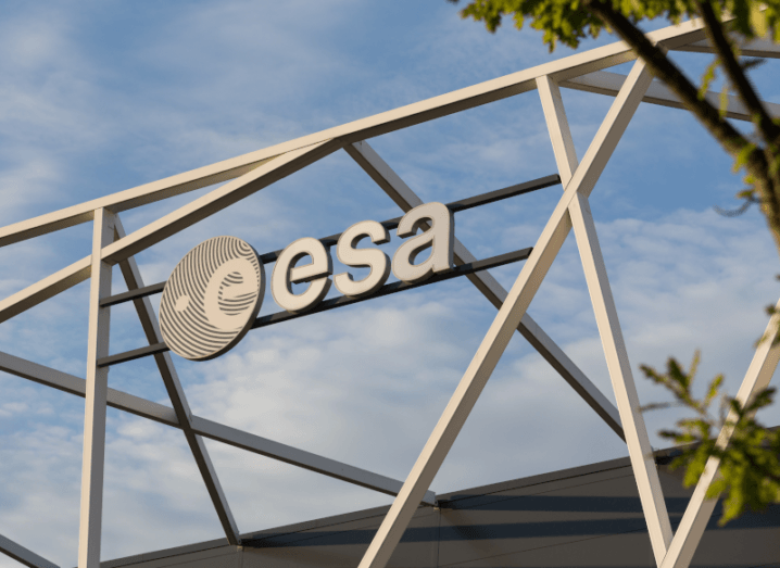 The ESA logo on a building, with a blue sky in the background.