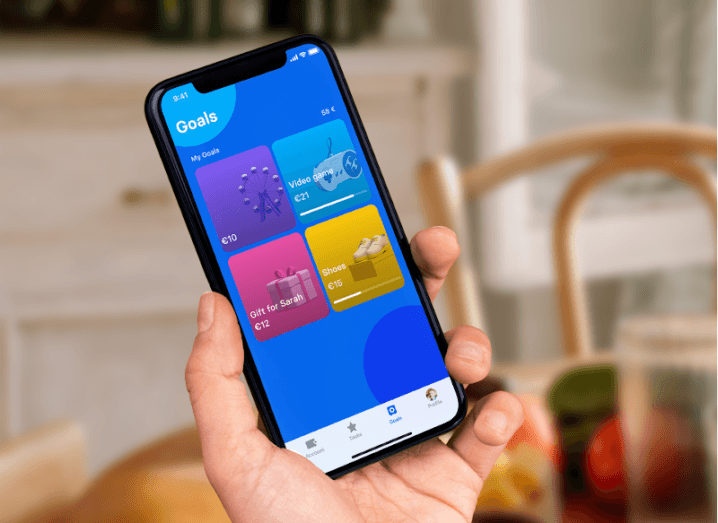 A child holding a smartphone with the Goals page displayed on the Revolut app.