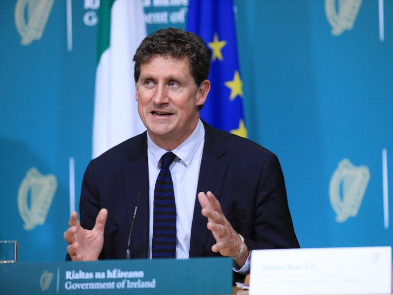 Eamon Ryan sits in a suit at a table during a government press conference.