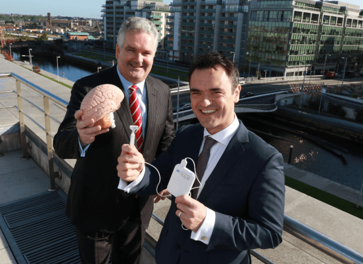 Two men standing on a balcony holding Neuromod's device for treating tinnitus.