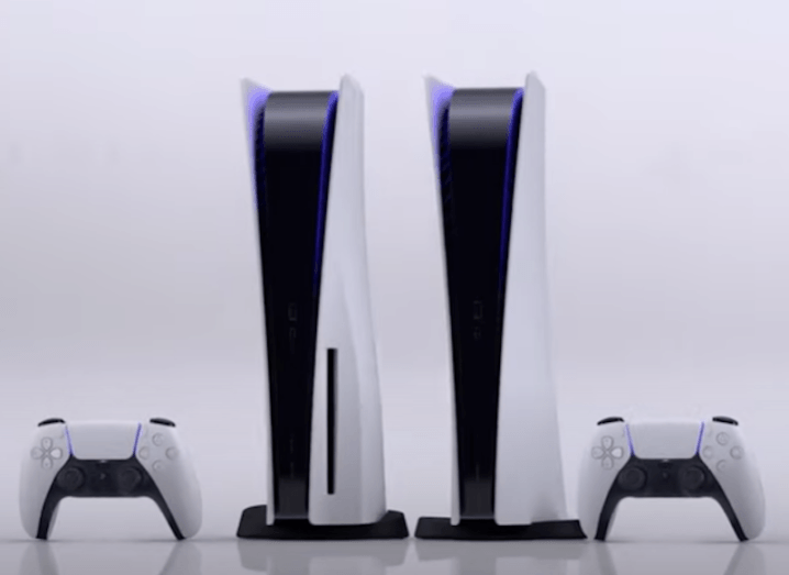 Two PS5 consoles and two controllers sitting against a white background.
