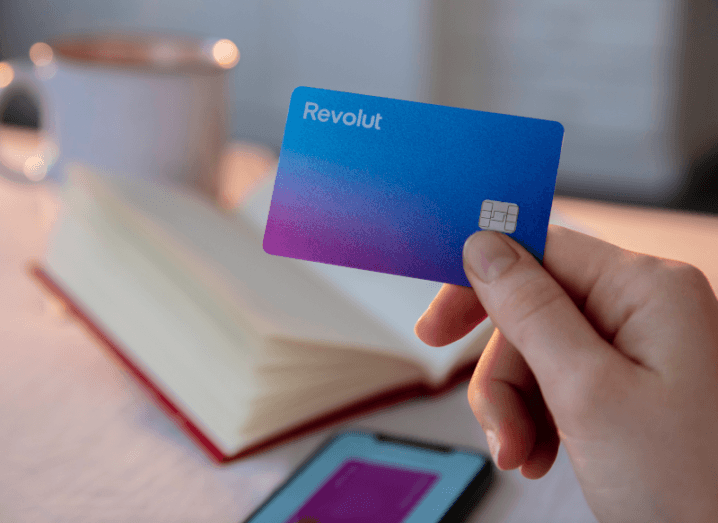 A person holding a Revolut card in front of a book and a mug.