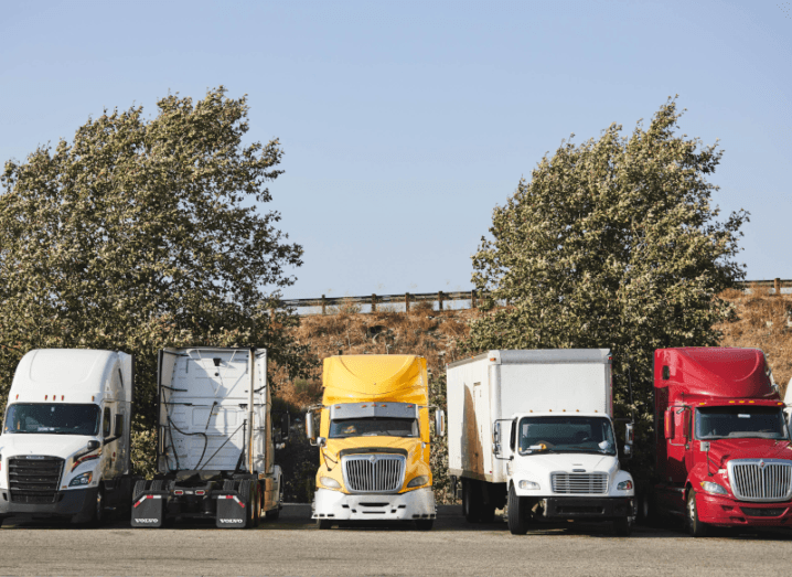 A line of trucks in a parking lot.