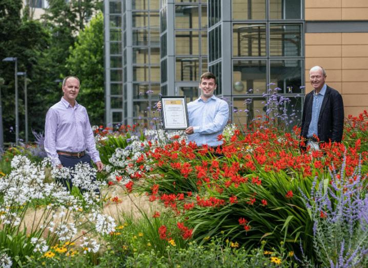 Three men standing in front of flowers.