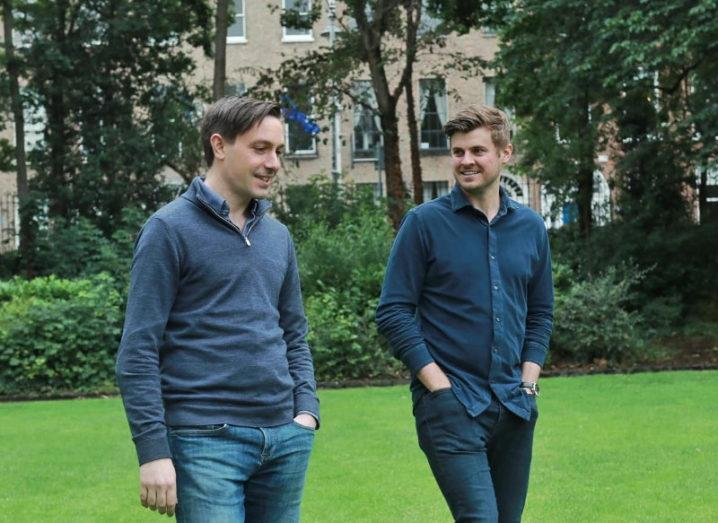 The co-founders of Wayflyer are walking and talking in a park.