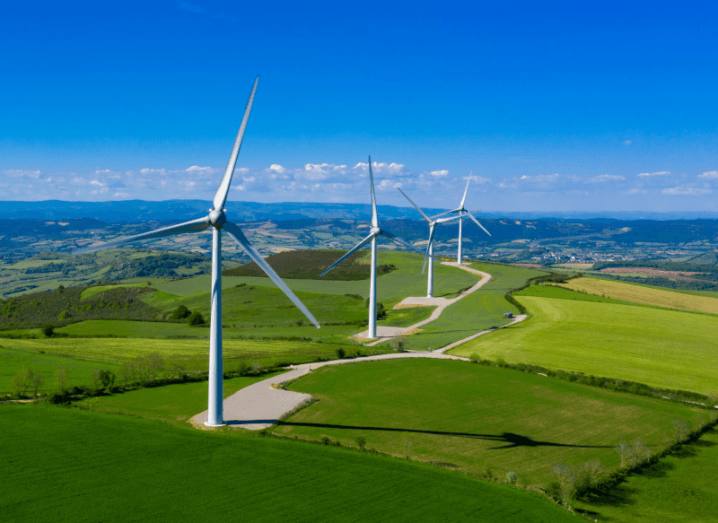 Large wind turbines in grass under a blue sky.