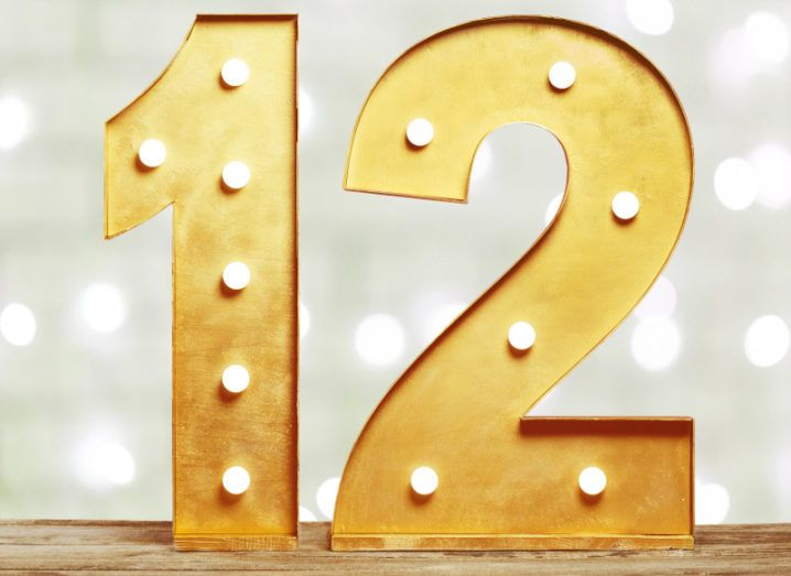 Golden three-dimensional number twelve lit up with shining lightbulbs against a twinkling background.