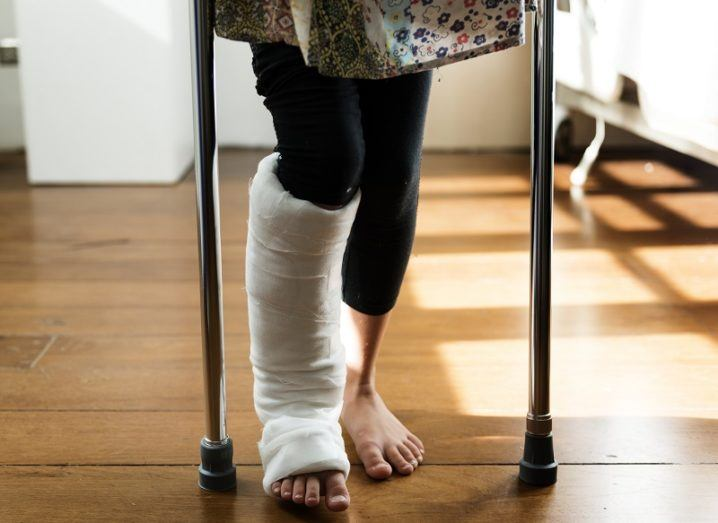 Woman with a cast on her leg trying to walk with crutches on a wooden floor.