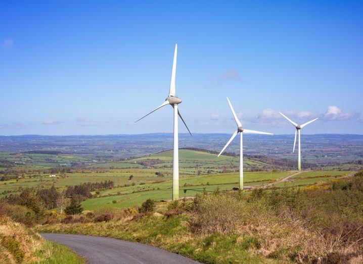 Three wind turbines in a rural area of Ireland against a clear blue sky.