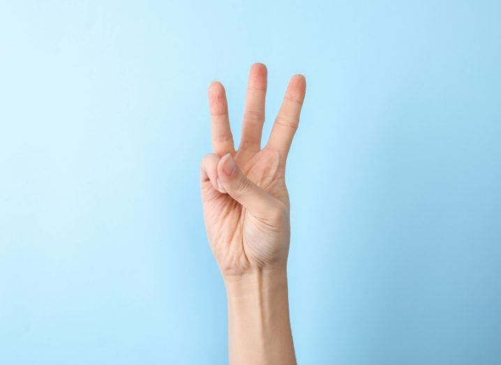 A hand holding up three fingers against a sky-blue background.