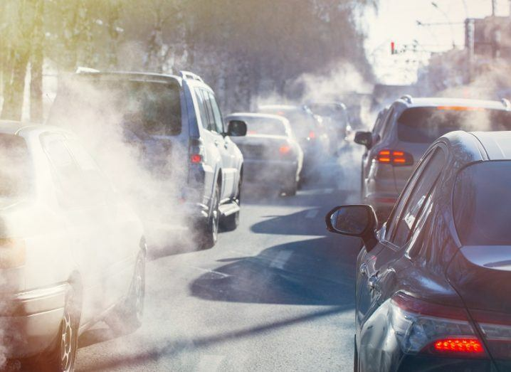 Cars waiting in traffic releasing emissions from exhausts.
