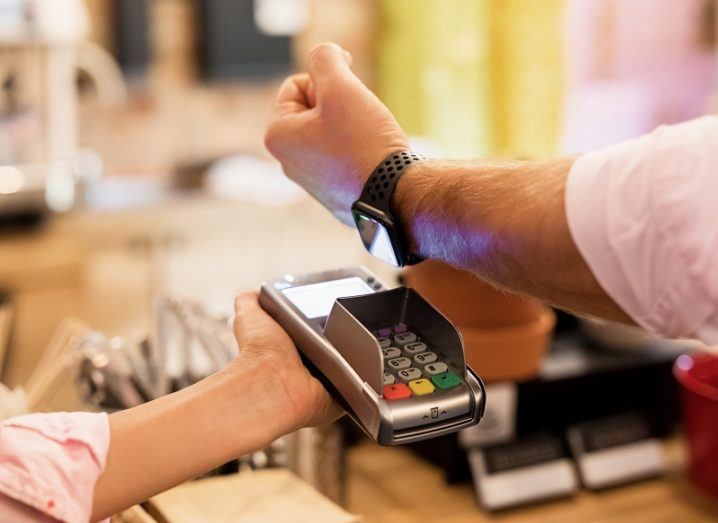 Person holding their Apple Watch over a payment terminal in a cafe.