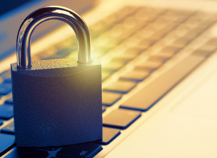 A padlock is sitting on a laptop keyboard, symbolising remote cybersecurity.