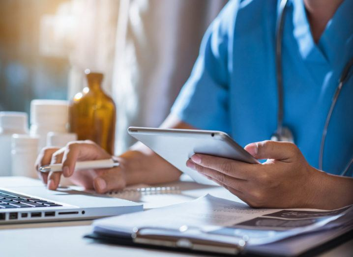 A doctor in scrubs is sitting at a desk and using a tablet, symbolising digital healthcare.